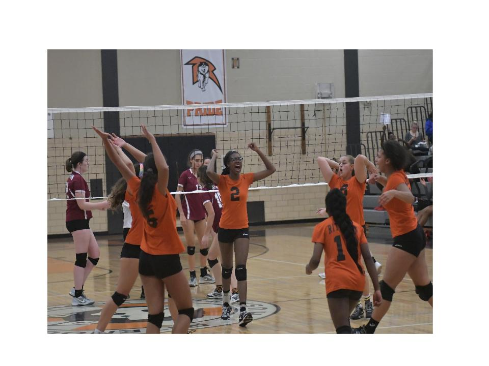 Varsity volleyball team celebrate after earning a point against Trinity Catholic.