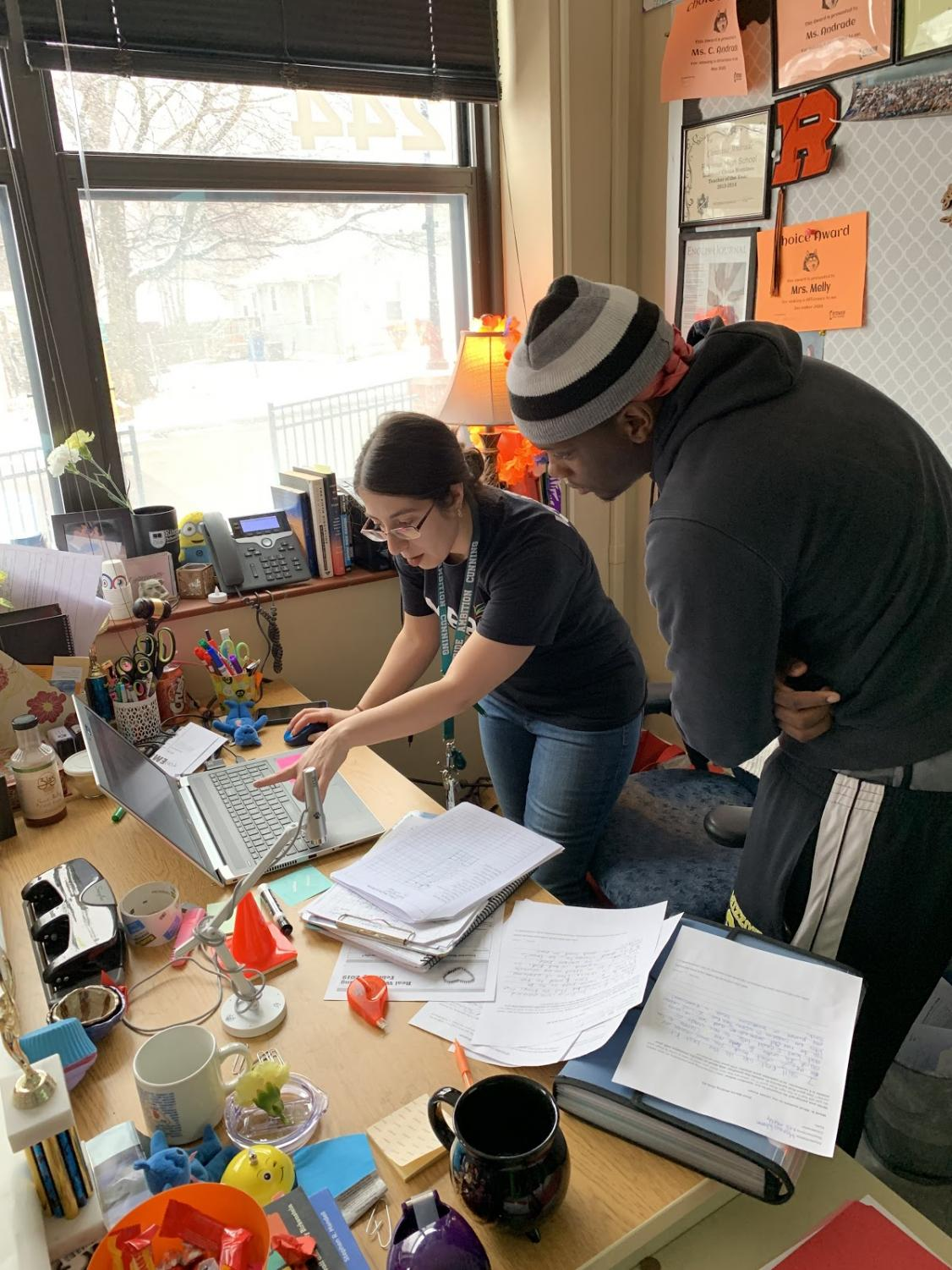 Teacher Christina Melly-Andrade aids in demonstrating a lesson to Markus Warren.